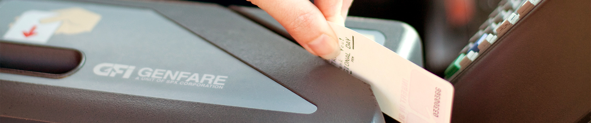 Hand swiping bus pass through onboard bus fare box