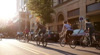 Bike riders travel down the street